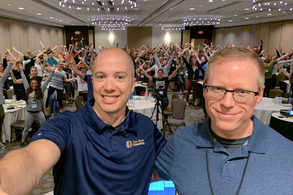 Josh Martin and Chris Cooper of Two-Brain Business stand in front of a large group of coaches whose arms are raised overhead.