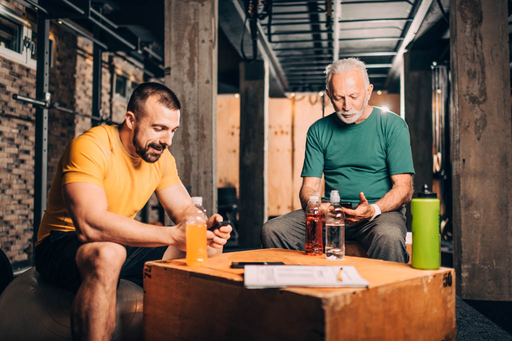 An older client and a younger personal trainer sit and log a workout with coaching software in a gym.