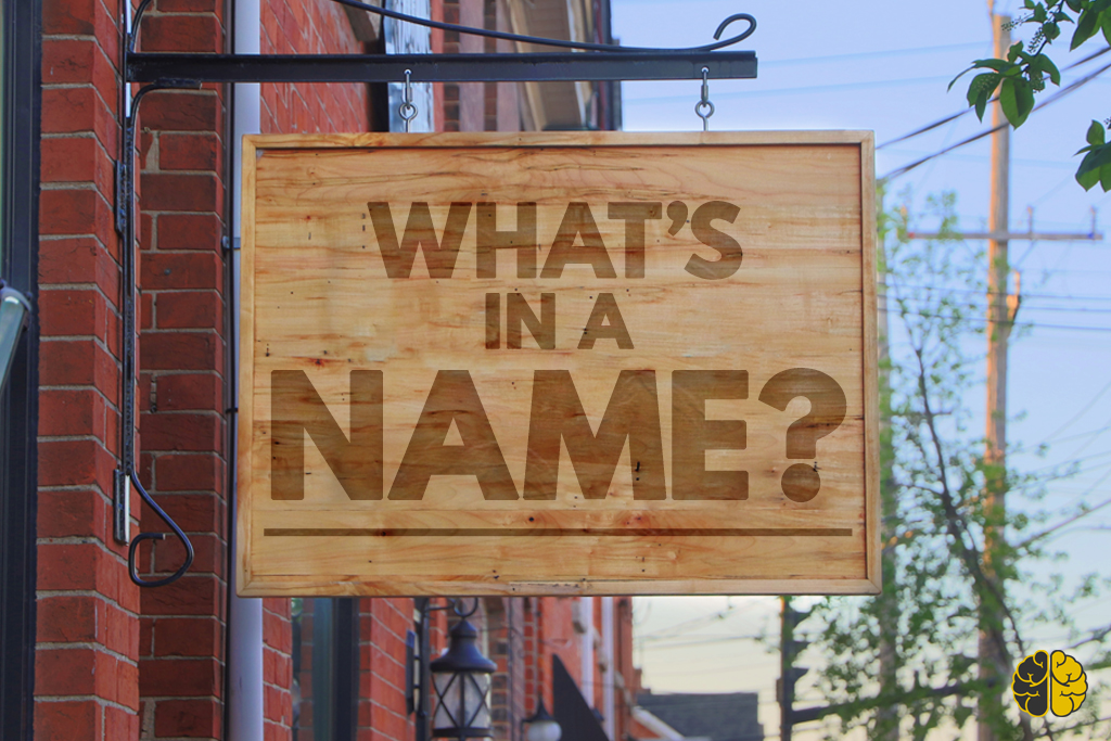 A wooden sign hanging outside a brick building inscribed 'What's In A Name?""