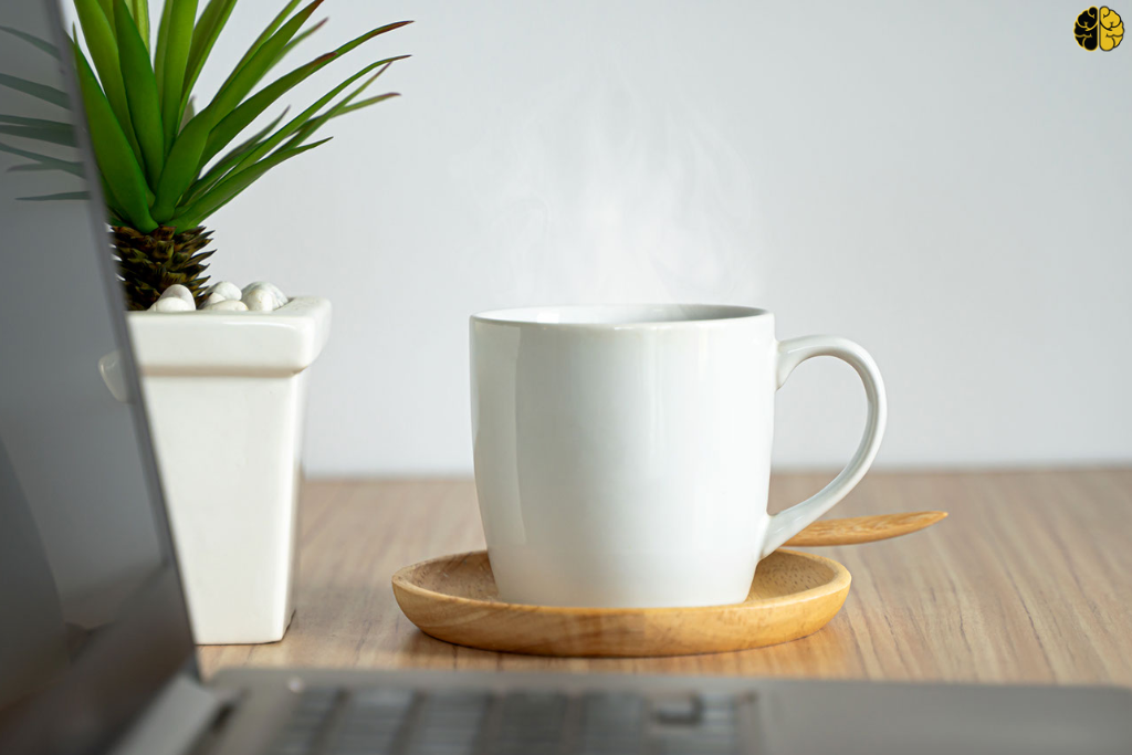 A mug of coffee next to a computer - the indirect ask