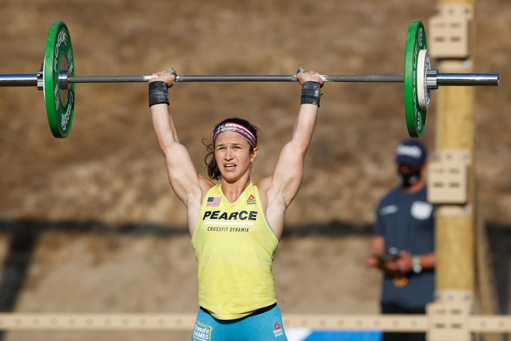 Kari Peace stands in a yellow top with a barbell overhead at the 2020 CrossFit Games.