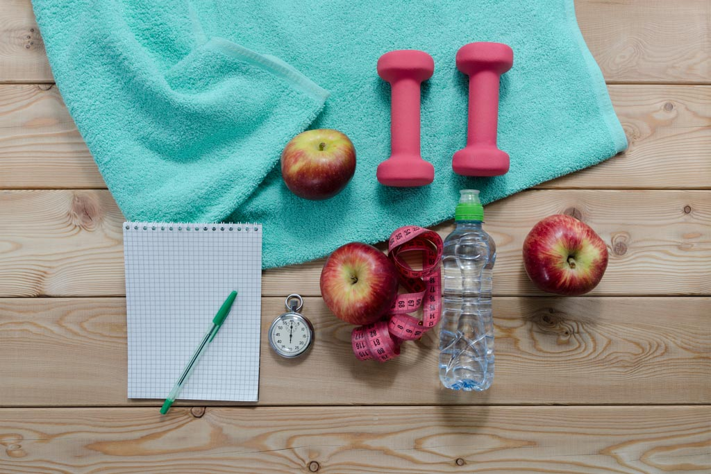 A notepad, some fruit, a dumbbell and a water bottle as seen from overhead.