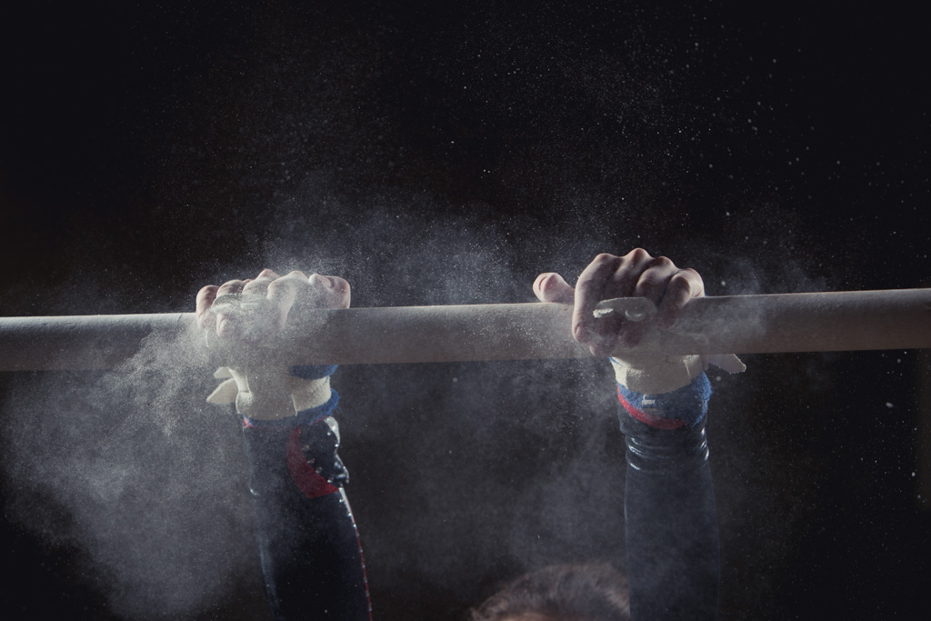 A gymnast's chalky hands grip the uneven bars at the start of a routine.