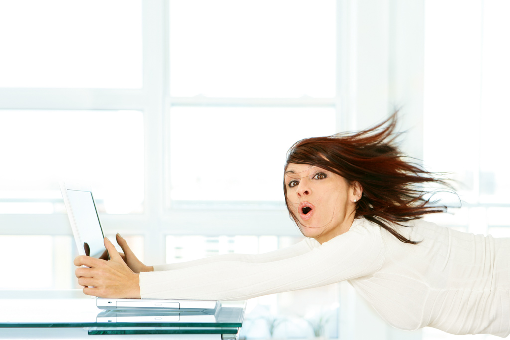 A woman holds onto her computer that's moving forward at very high speed.